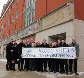 Owners of Skyline stand outside an apartment building holding a sign that says 10,000 suites and growing