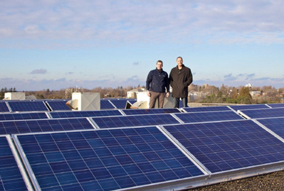 Two men stand on a rooftop amongst solar panels
